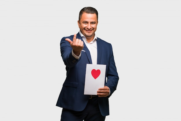 Middle aged latin man celebrating valentines day inviting to come