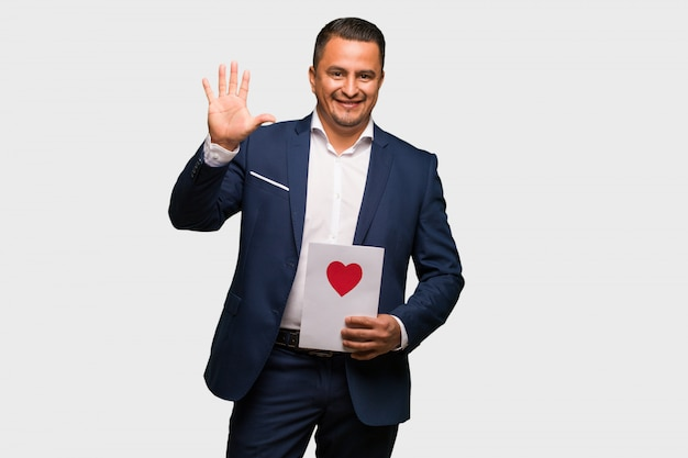 Middle aged latin man celebrating valentines day showing number five