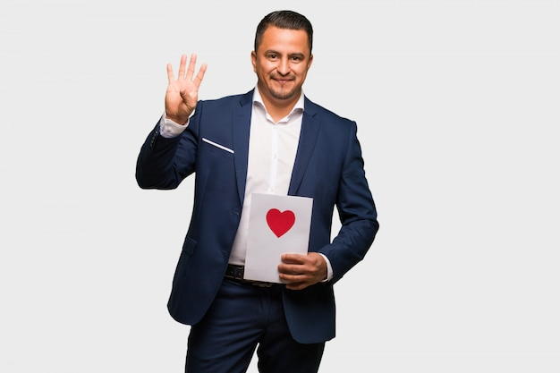 Middle aged latin man celebrating valentines day showing number four