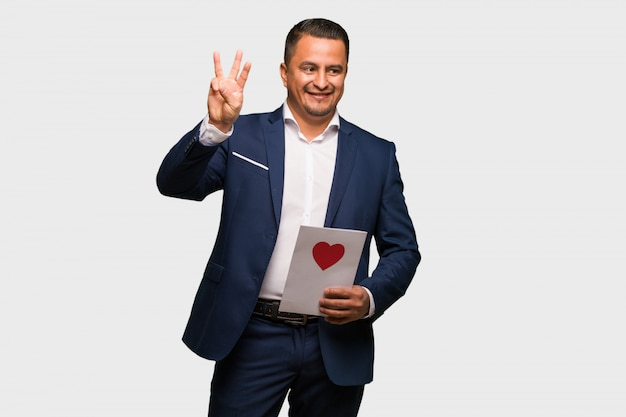 Middle aged latin man celebrating valentines day showing number three