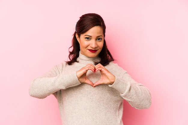 Middle aged latin woman isolated on a pink wall smiling and showing a heart shape with hands