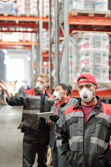Middle aged latino male worker in uniform and protective respirator standing in front of camera in warehouse against his colleagues