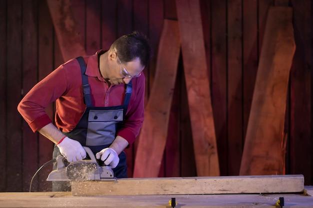 Плотник средних лет обрабатывает деревянную заготовку электрическим рубанком на верстаке в дачной мастерской. плотницкие работы по дереву. работа в загородном доме.