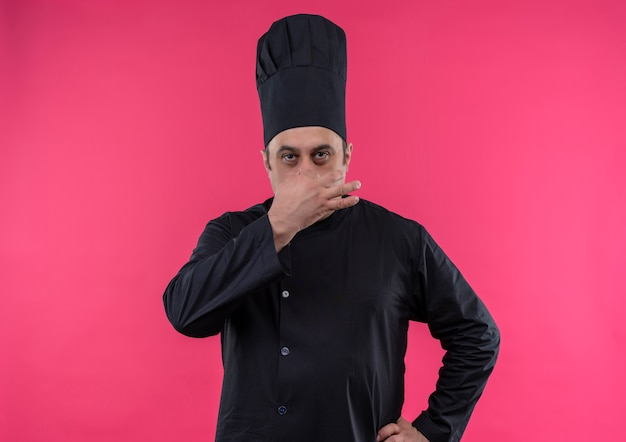 Middle-aged male cook in chef uniform closed nose on isolated pink wall