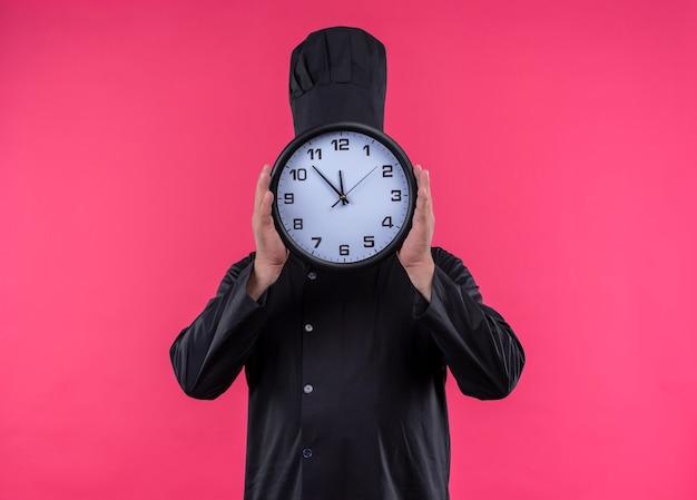 Cuoco maschio di mezza età in uniforme del cuoco unico coperto il fronte con l'orologio di parete sulla parete rosa isolata con lo spazio della copia