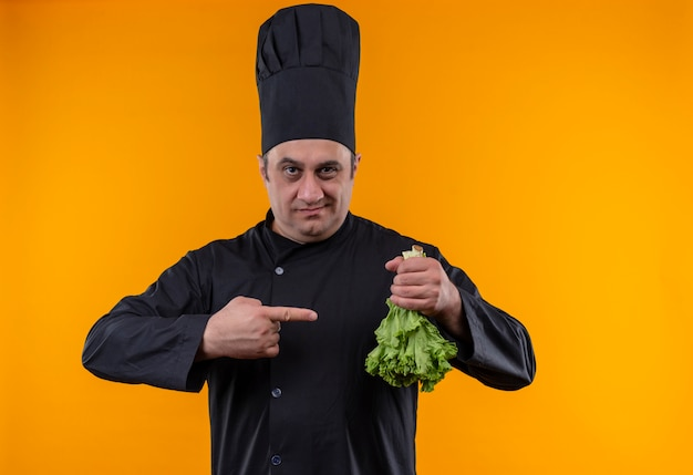 Middle-aged male cook in chef uniform points finger to salad in his hand on yellow wall with copy space