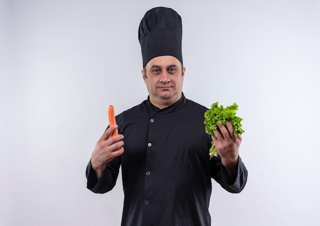 孤立した白い壁にニンジンとサラダを保持しているシェフの制服を着た中年男性料理人