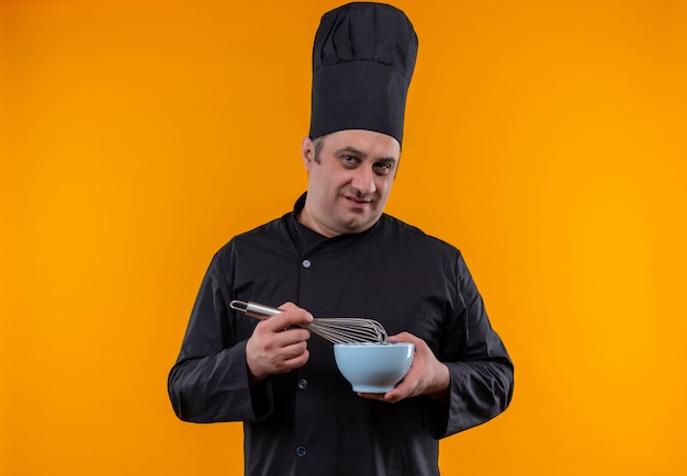 黄色の壁に泡立て器とボウルを保持しているシェフの制服を着た中年男性料理人