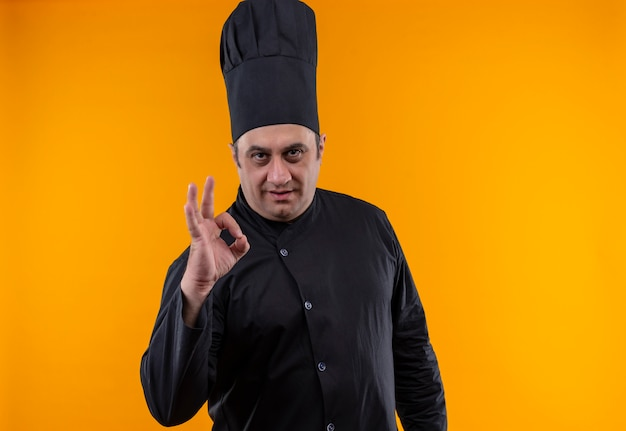 Мужчина средних лет повар в униформе шеф-повара показывает жест на желтой стене