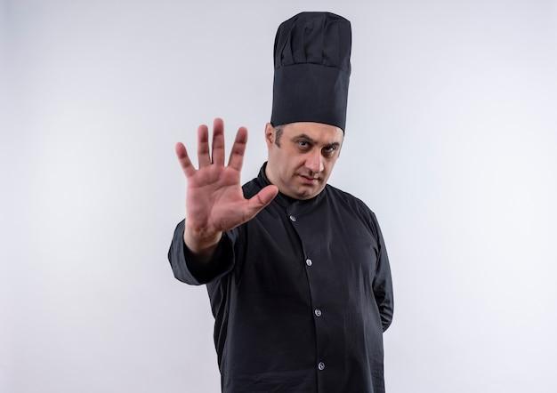 孤立した白い壁に停止ジェスチャーを示すシェフの制服を着た中年男性料理人