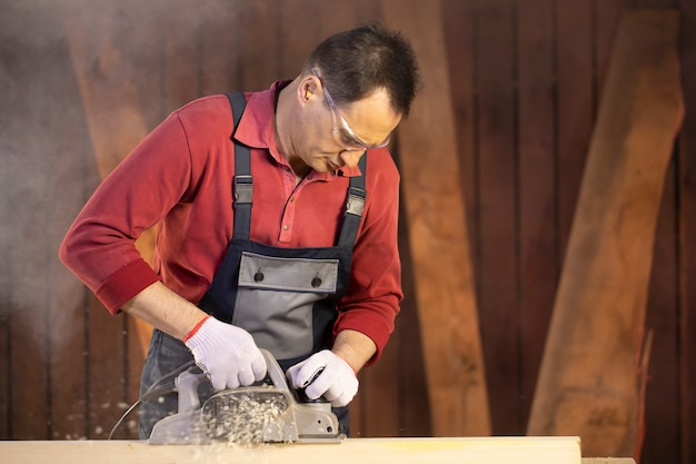 Middle-aged male craftsman in googles treats piece of wood with electric planer