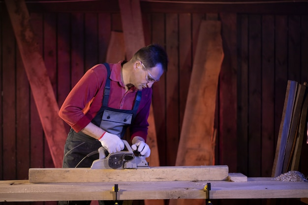 Middle-aged male craftsman treats wooden workpiece with electric planer