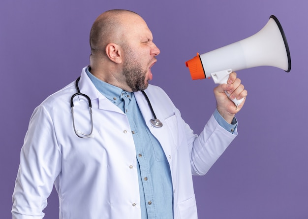 Middle-aged male doctor wearing medical robe and stethoscope looking at side shouting in loud speaker isolated on purple wall