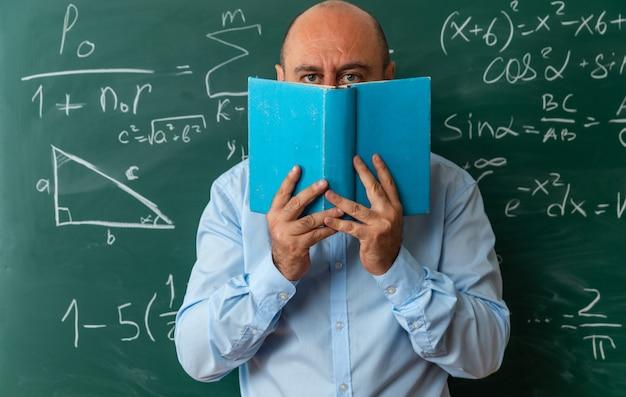 Insegnante maschio di mezza età in piedi davanti al viso coperto di lavagna con libro