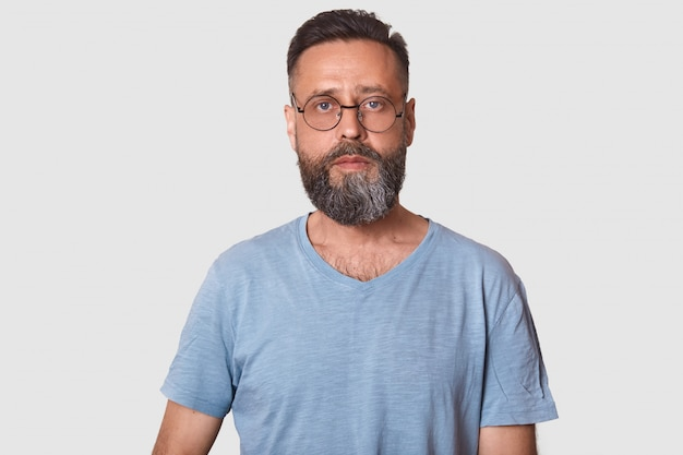 Middle aged male wearing eyeglasses and caual gray t shirt, posing on white with copy space, guy with beard. people concept.