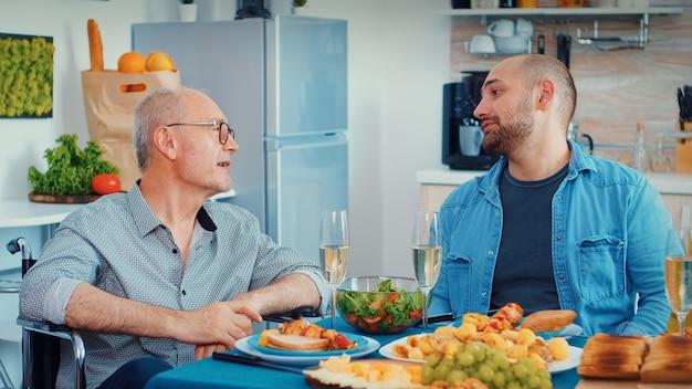 家族の夕食を楽しんでいる車椅子の中年男性と年配の先輩。グルメな食事の間に笑顔、飲酒、食事、キッチンのテーブルの周りに座って時間を楽しんでいる幸せな男性