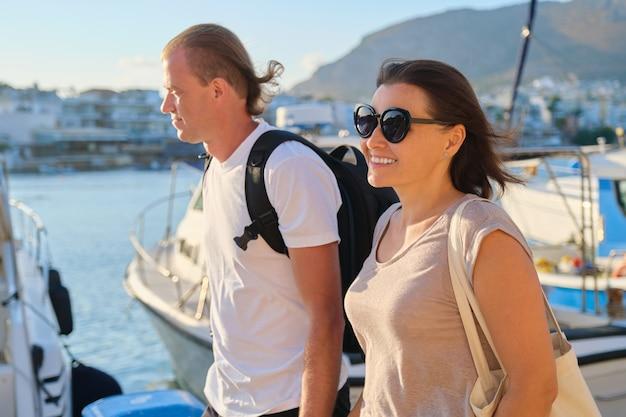Мужчина и женщина средних лет гуляют вместе, держась за руки