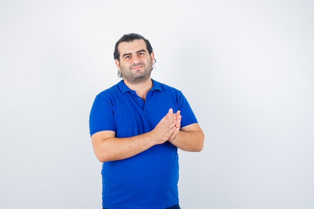 青いtシャツで拍手と幸せそうに見える中年男性、正面図。