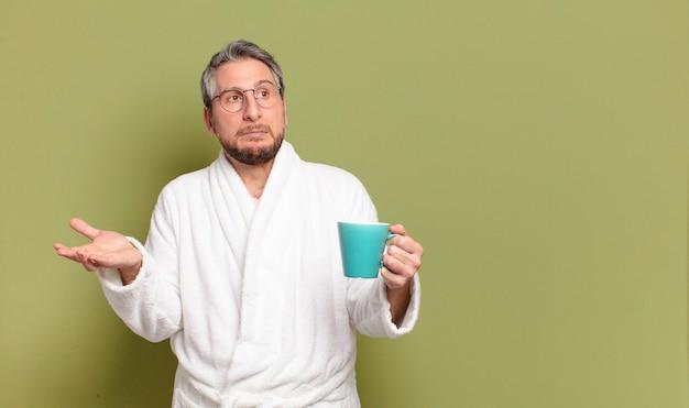 Мужчина средних лет просыпается с чашкой кофе