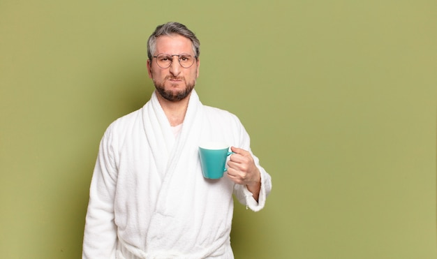 Middle aged man awaking with a coffee cup