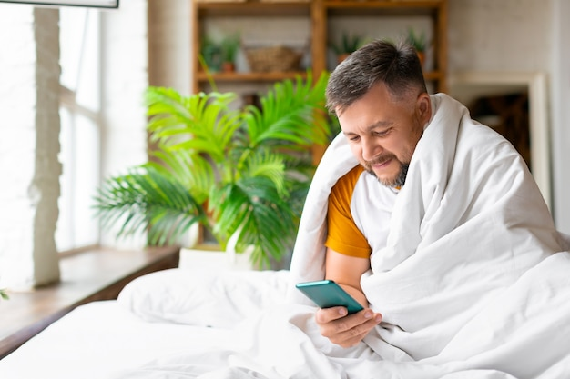 Middle aged man in bed checking his messages in smartphone after awakening addiction to social netwo...