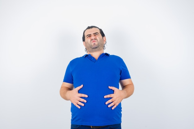 Middle aged man in blue t-shirt holding hands on stomach and looking unwell , front view.