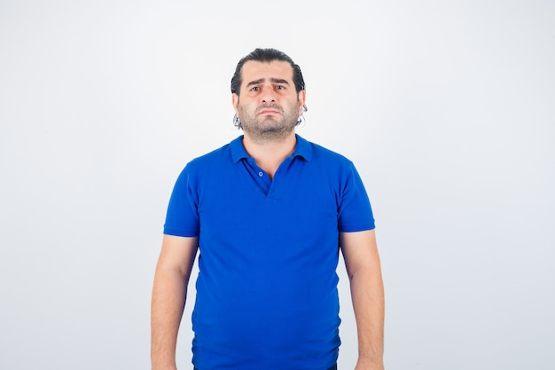 Middle aged man in blue t-shirt looking at camera and looking wistful , front view.