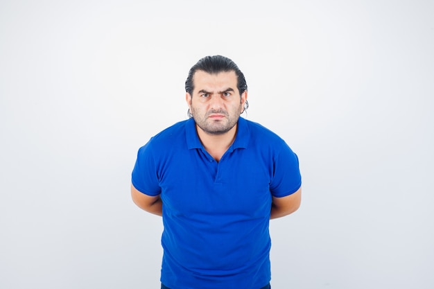 Uomo di mezza età in maglietta blu che guarda l'obbiettivo tenendo le mani dietro la schiena e guardando serio, vista frontale.