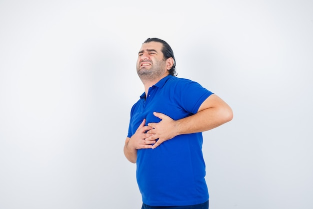 Middle aged man in blue t-shirt suffering from heart pain and looking unwell , front view.