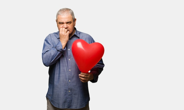 Middle aged man celebrating valentines day biting nails, nervous and very anxious