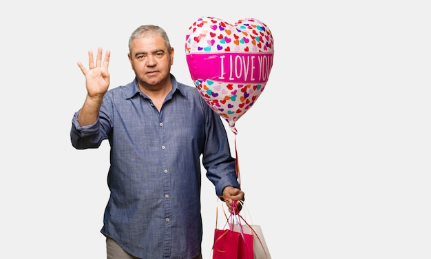 Middle aged man celebrating valentines day showing number four