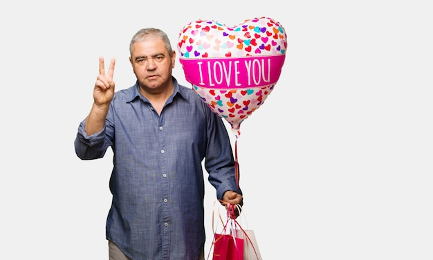 Middle aged man celebrating valentines day showing number two