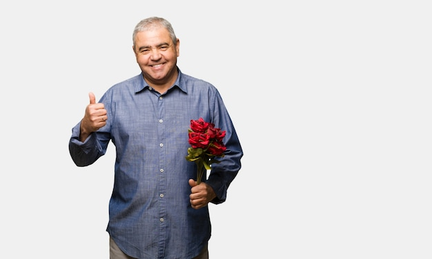 Middle aged man celebrating valentines day smiling and raising thumb up