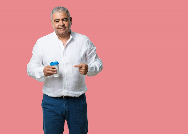 Middle aged man cheerful and vital, holding a coffee to go, take away beverage, concept of