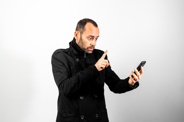Middle-aged man in coat with astonishment gesture while talking on his mobile phone, isolated on white.