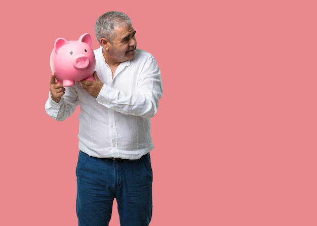 Middle aged man confident and cheerful, holding a piglet bank and being quiet