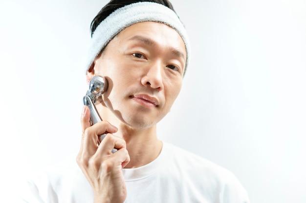 Мужчина средних лет делает небольшой массаж лица с помощью инструмента