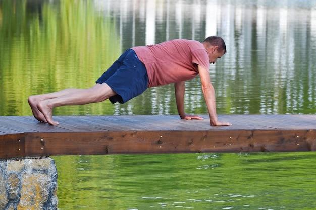 Middle aged man doing yoga asanas. male athlete trains on pier outside park.