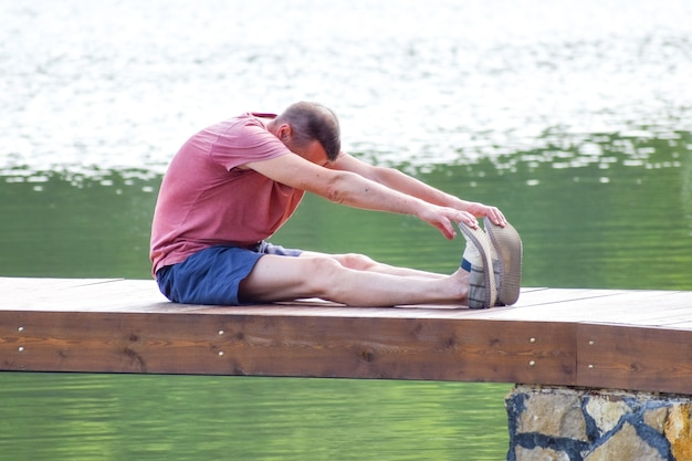 Middle aged man doing yoga asanas. a male athlete trains on the pier outside in the summer park.