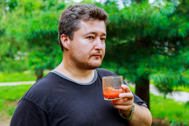 Middle aged man drinks tomato juice on the street