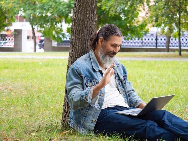 Мужчина средних лет во время онлайн-видеозвонка сидит на траве в городском парке с ноутбуком, ...