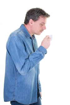 Middle-aged man enjoying smell of hot beverage tea or coffee anticipating the sweet taste and looking