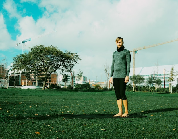 ヨガマットを使用して公園でヨガ、ストレッチ、運動、トレーニングの準備をしている中年男性。自然な初心者のヨガのポーズ。ヘルスケアの概念。