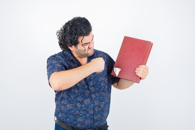 중간 세 남자 셔츠에 책을 펀치를 준비 하 고 화가, 전면보기를 찾고.