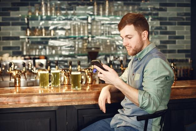 中年の男。バーで電話を持っている男。セルのデニムシャツを着た男。
