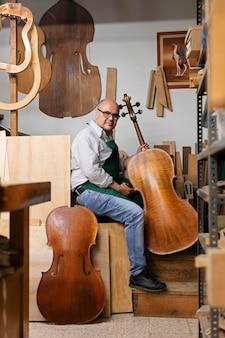 Uomo di mezza età nel suo laboratorio di strumenti