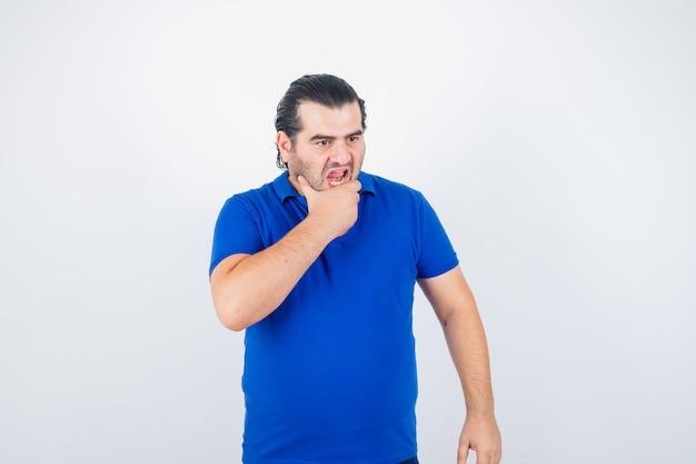 Uomo di mezza età che tiene la mano sul mento in maglietta blu e che sembra arrabbiato. vista frontale.