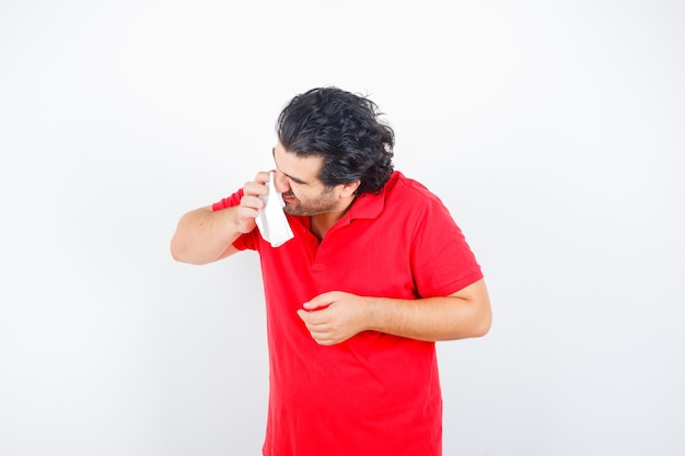 Middle aged man holding handkerchief blowing running nose in red t-shirt and looking unhealthy , front view.