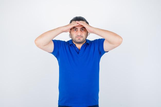 Uomo di mezza età che tiene le mani sulla testa per vedere chiaramente in maglietta blu e guardando serio, vista frontale.
