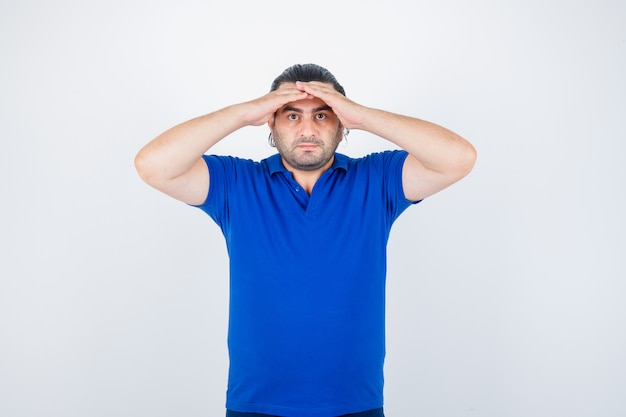 青いtシャツではっきりと見えるように頭に手をつないで真面目な中年男性、正面図。